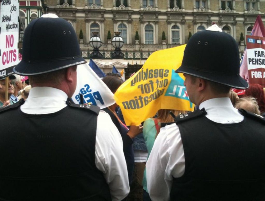 Policemen look on during the public sector strike march
