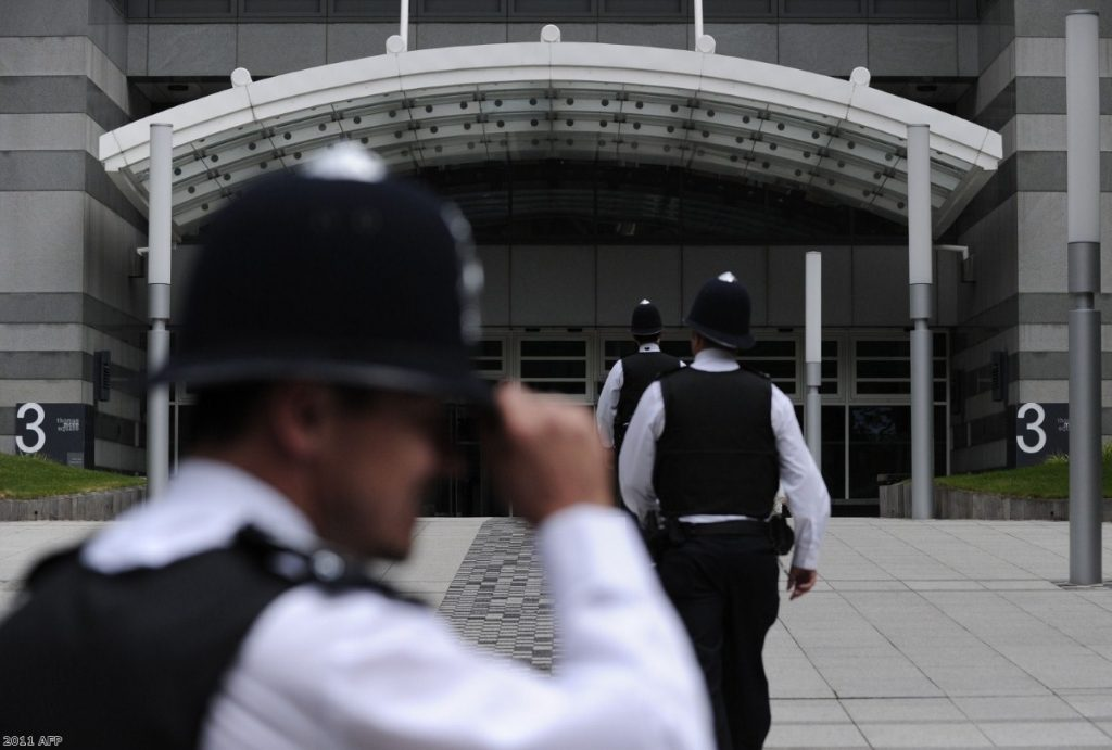 Police officers stand outside the News International offices in east London over the weekend