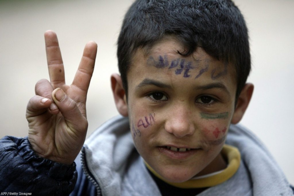 A young Syrian refugee who fled  the violence in Homs flashes the 'V for victory' sign as he takes shelter in northern Lebanon