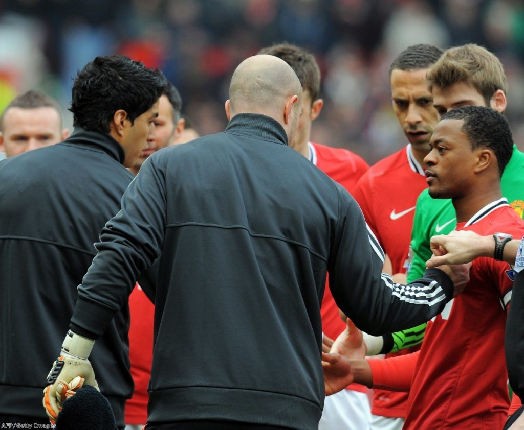 Rio Ferdinand looks disgusted as Suarez fails to shake Evra's hand