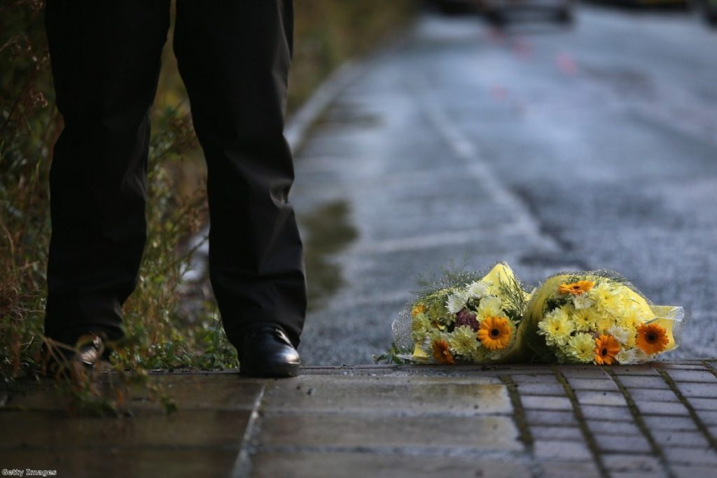 A police officer stands next to a tribute of flowers given by a member of the public in Hattersley, Tameside at the corden where two female police officers were shot.