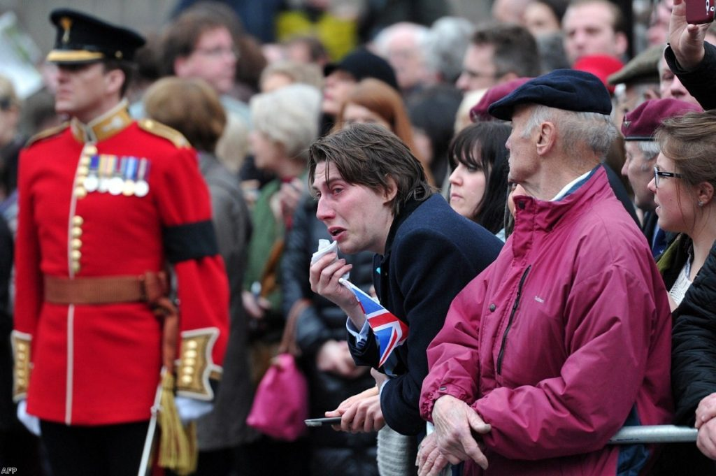 A mourner weeps as Margaret Thatcher's coffin is brought to St Paul's cathedral
