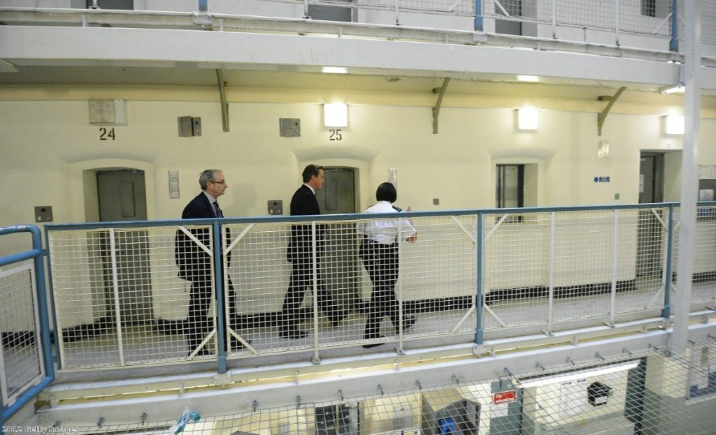 David Cameron is escorted around the Scrubs in 2012. Since then suicides at the prison have shot up.