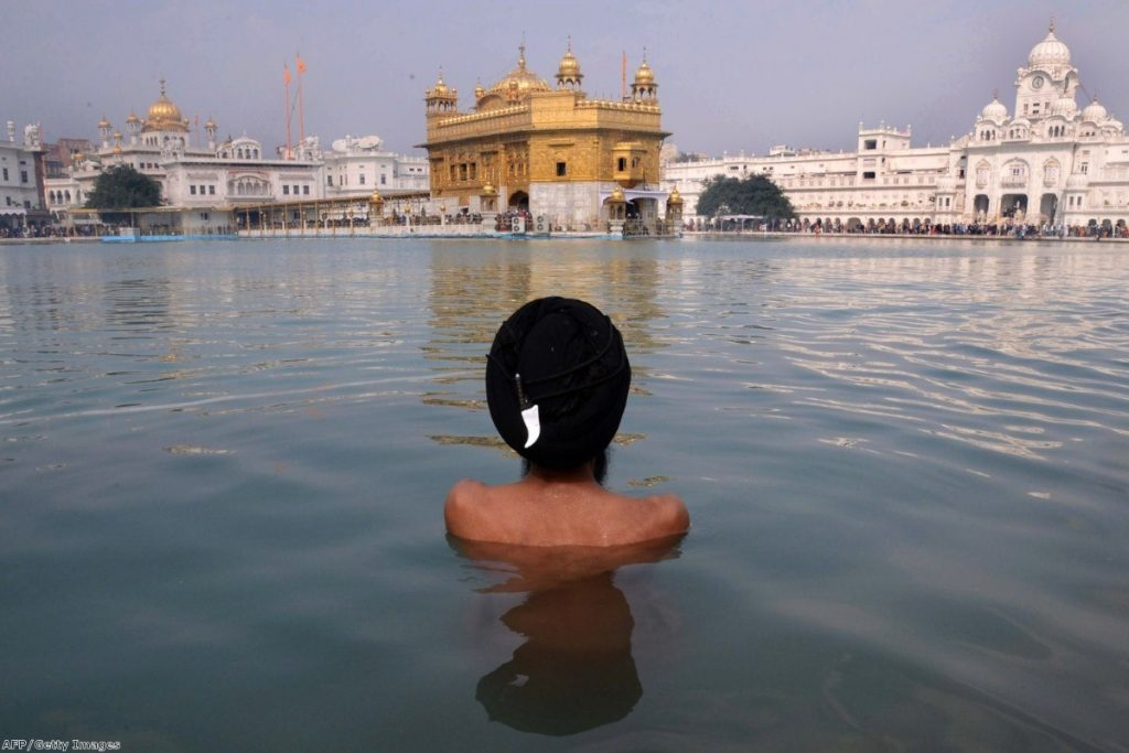 A Sikh takes a dip in the holy sarover at the Golden Temple in Amritsar last Tuesday. The massacre was a defining moment for many Sikhs around the world.