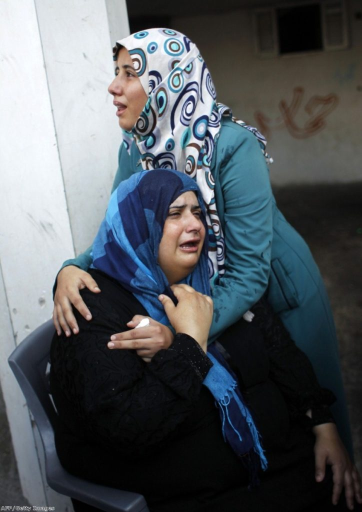 Relatives mourn during a funeral of at least nine members of the same al-Ghul family who died after their house was hit by an Israeli air strike yesterday