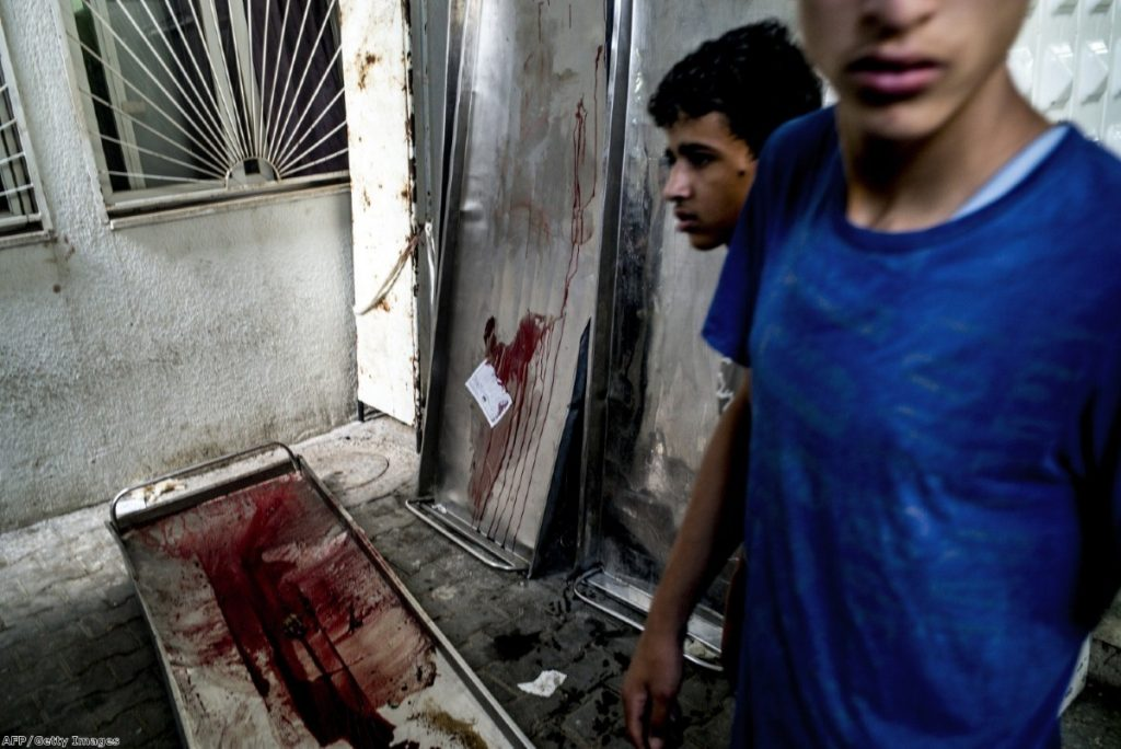 Blood-stained gurneys are seen outside the morgue at the Kamal Adwan hospital in Beit Lahia, as members of the Abu Nejim family gather to collect their family members killed in an airstrike on their house on Monday