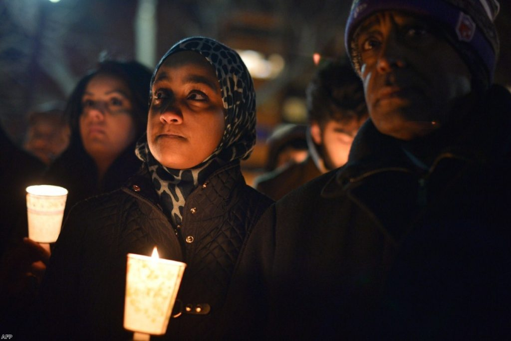 People hold candles during a vigil for three young Muslims killed in Chapel Hill, North Carolina, last night in Washington