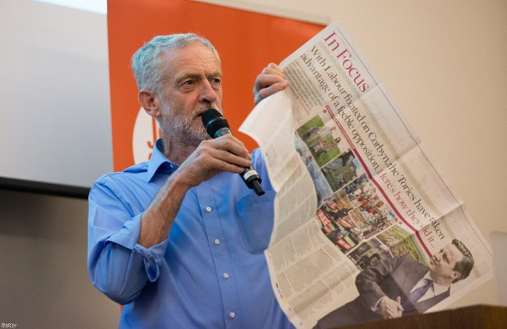 Jeremy Corbyn holds up a newspaper article as he speaks at a rally for supporters on August 25, 2015 in Southampton