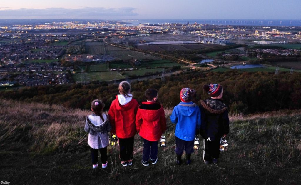 Children stand with lanterns during a torch-lit procession on the top of the Eston Hills overlooking Teesside