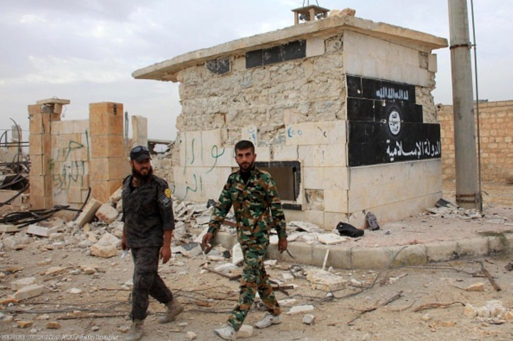 Syrian government forces walk past a building bearing an image on the wall with Islamic writing and reading in Arabic the 'Islamic State'