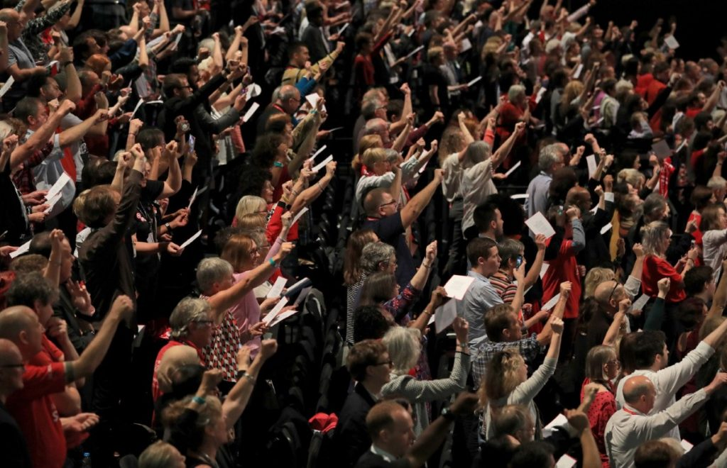 Delegates hold up their fists as they sing the Red Flag after Corbyn's speech