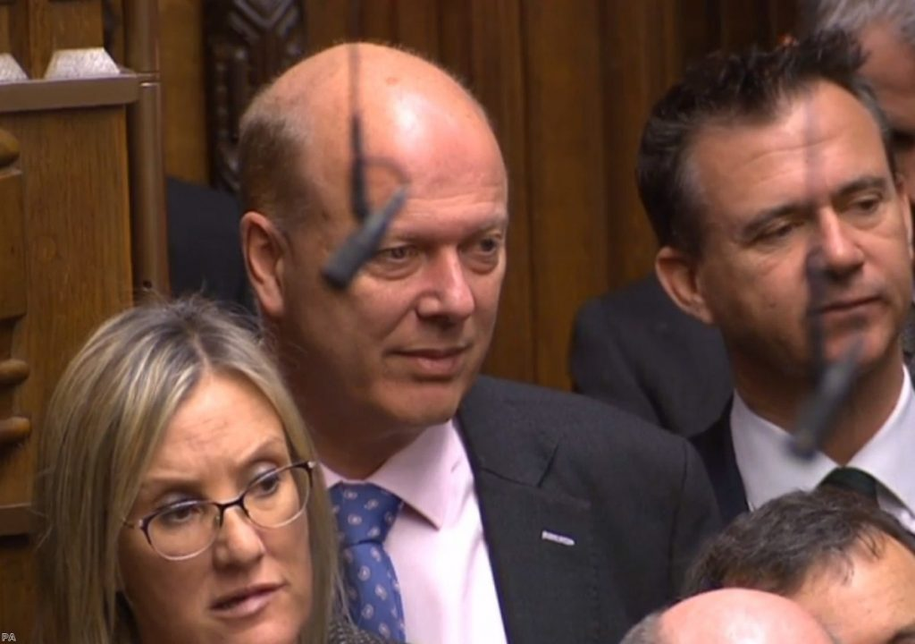 Chris Grayling watches on during PMQs. The transport secretary fails either upwards or sideways.