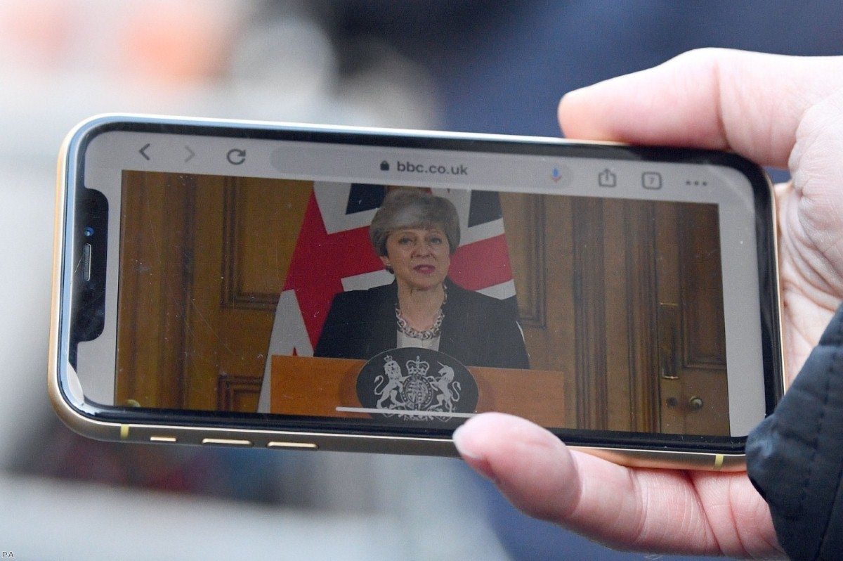 A journalist watches the prime minister's statement on a mobile phone this afternoon
