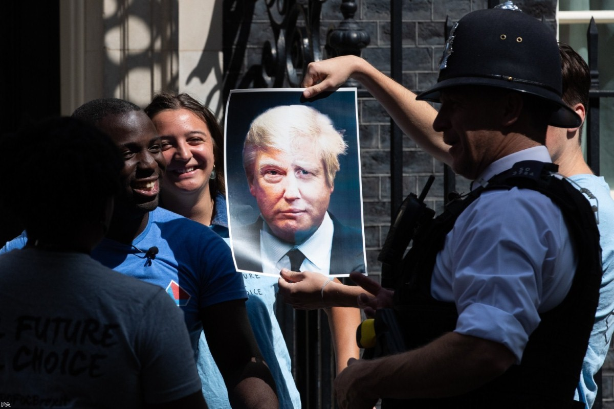 Campaigners for the youth group Ofoc hold up a poster melding Johnson and Trump's face as they hand in a petition to Downing Street.