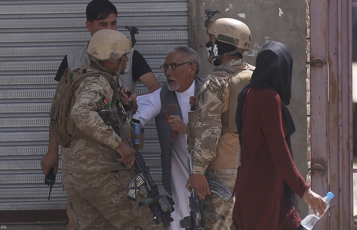 Afghan security officers stop a man near the site of an explosion in Kabul last Wednesday.