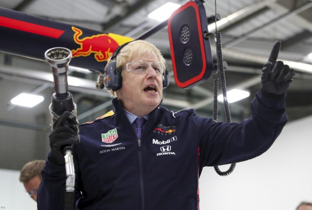 Boris Johnson prepares to change a wheel during a visit to Red Bull Racing facility in Milton Keynes. He has been accused of lying and evasiveness during the campaign.