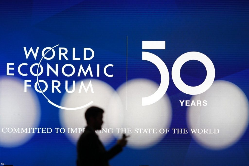 A man silhouettes in front of the logo of the World Economic Forum in Davos, Switzerland, on Sunday.