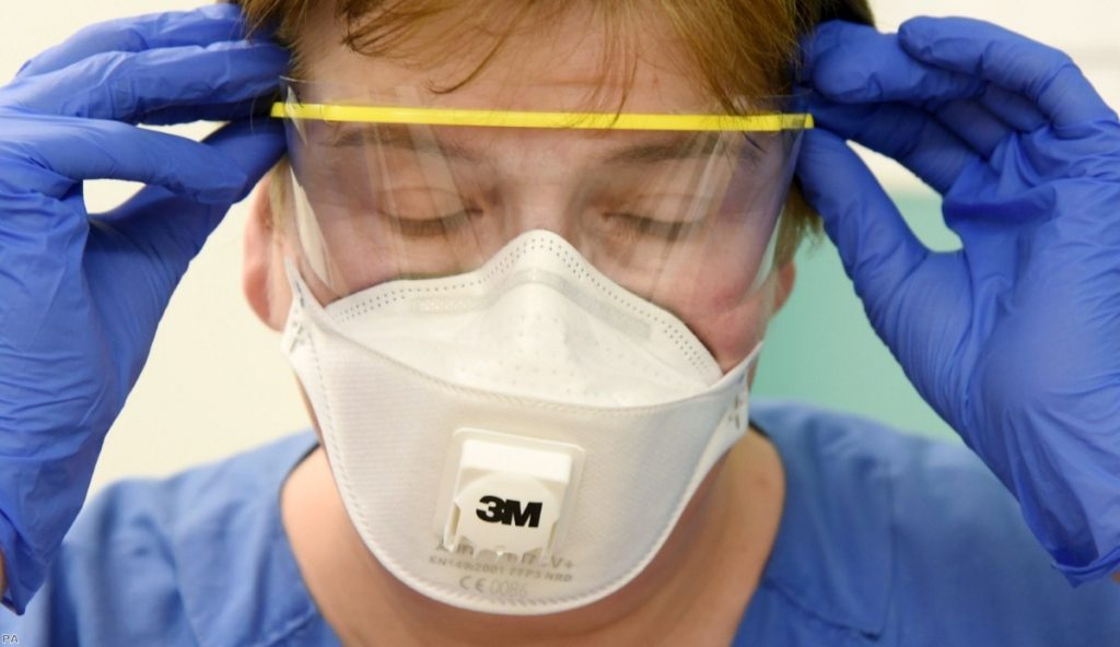 A nurse wearing wearing protective equipment puts on her goggles at the Clinic for Infectiology/Tropical Medicine, Nephrology and Rheumatology in Leipzig.