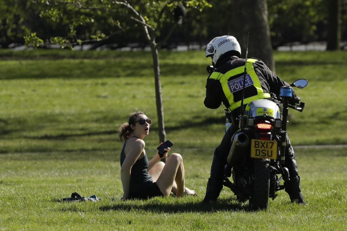 A woman is told to go home by a police officer on Primrose Hill in London last weekend.