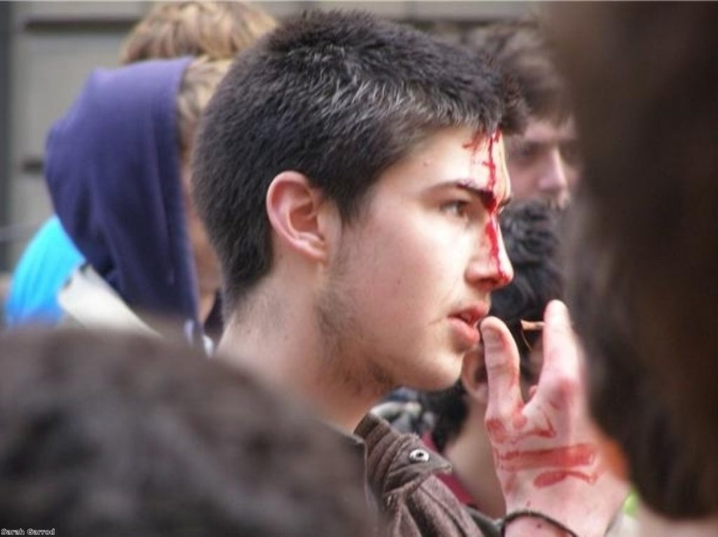 A protestor with blood on his face stares at police lines during the 2009 G20 demonstration in London.