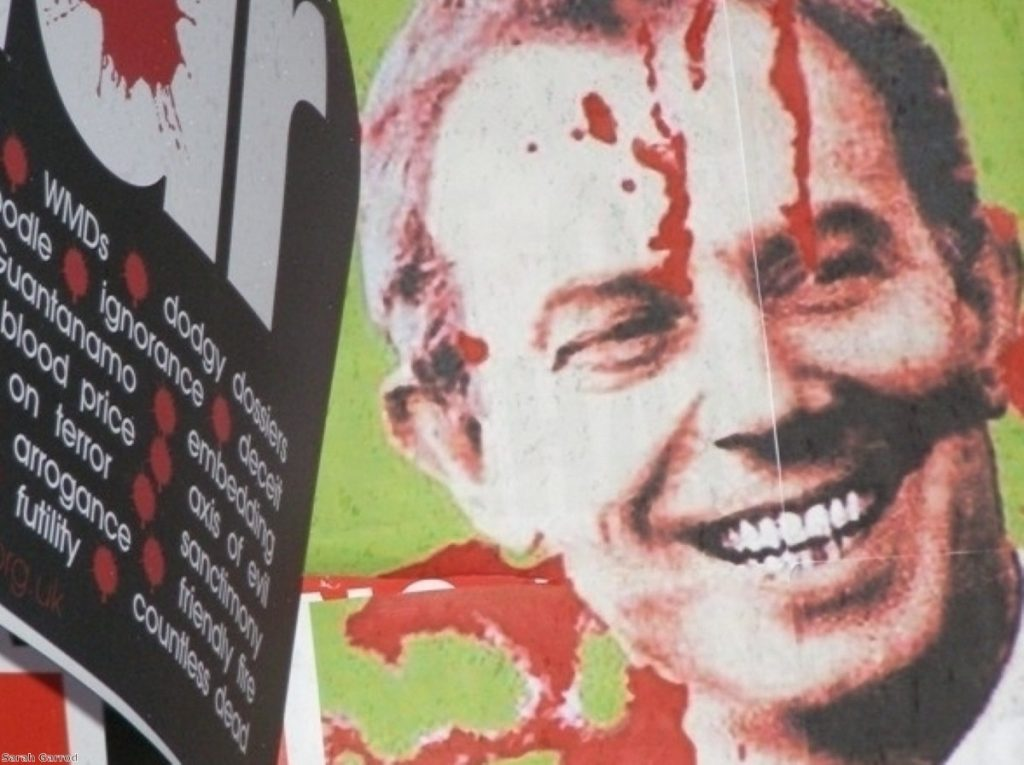 A protestor holds  up an anti-Blair banner during his last evidence session