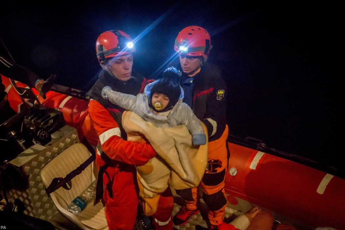 A young child is rescued from a boat by the crew of the Alan Kurdi rescue ship, operated by German charity Sea-Eye, in December last year.