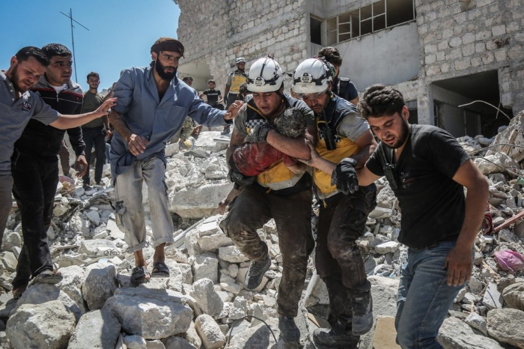 Members of the White Helmets in Syria carry an injured but alive child from the rubble of a collapsed building following pro-regime air strikes in summer last year.