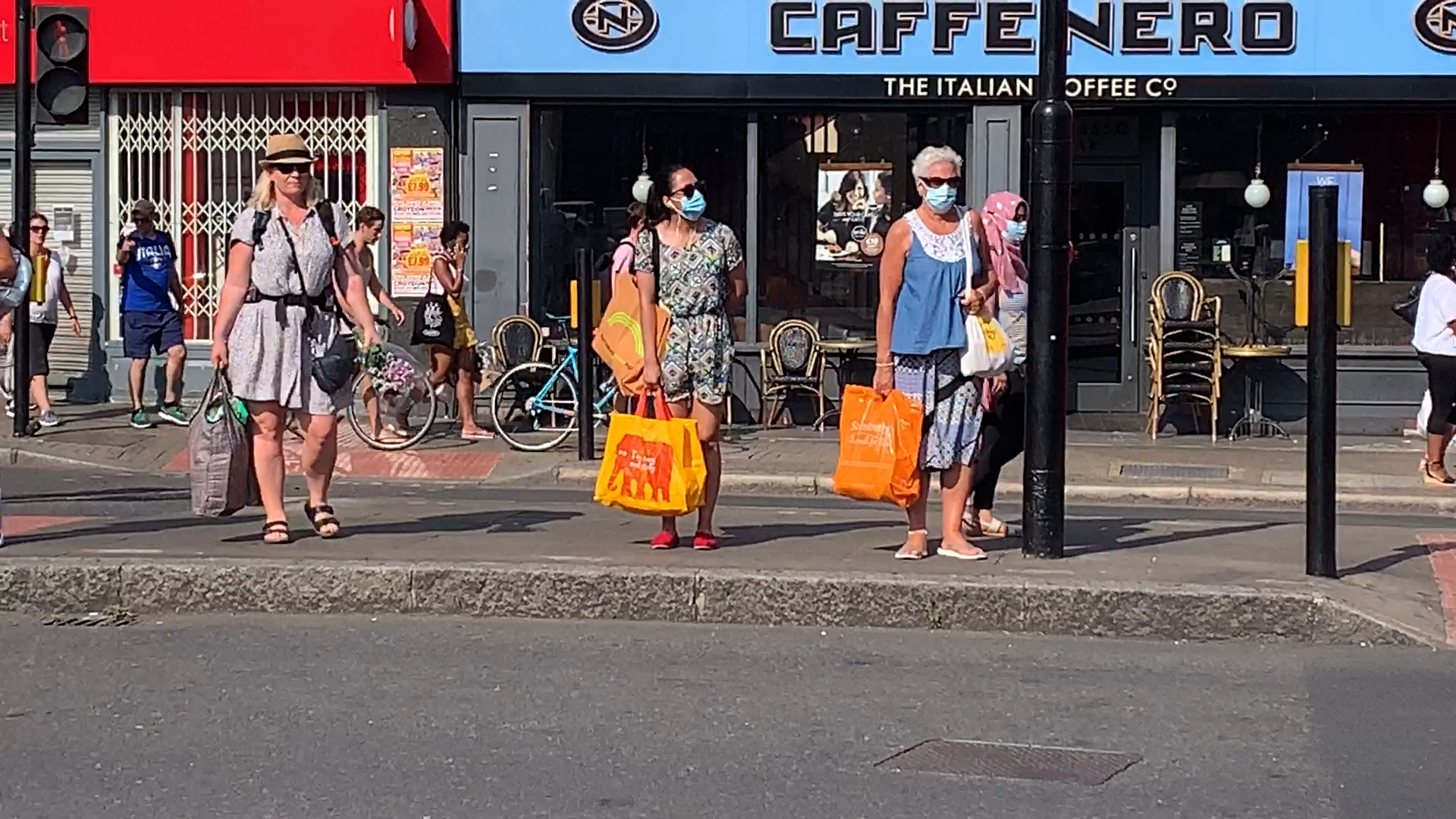 People standing at traffic lights wearing face masks