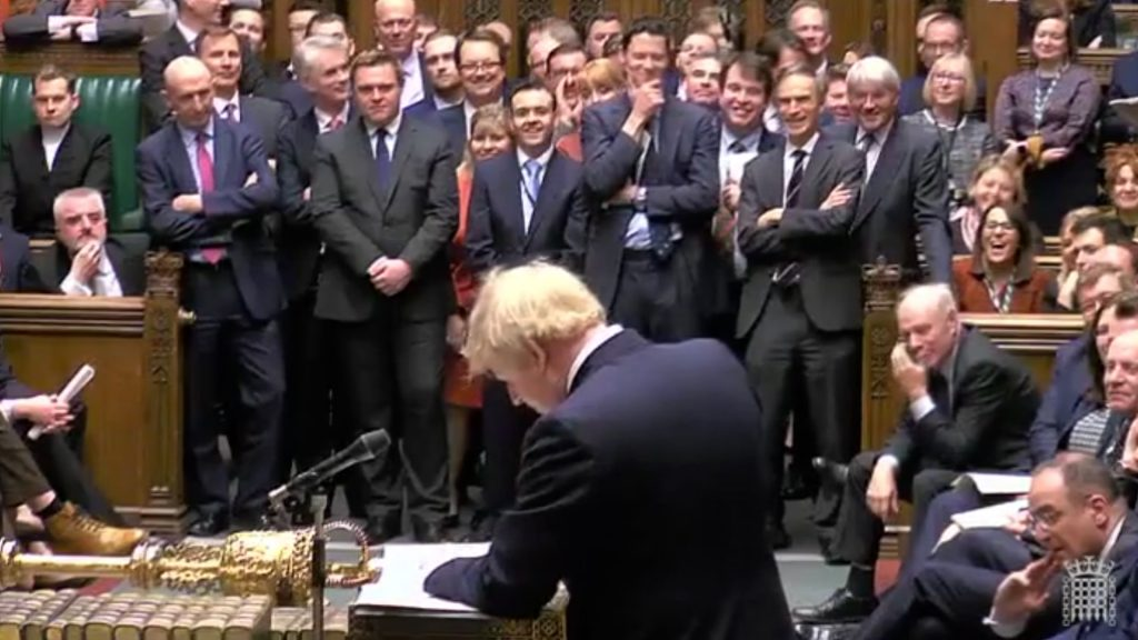 Boris Johnson standing at the despatch box in the House of Commons in front of a group of MPs